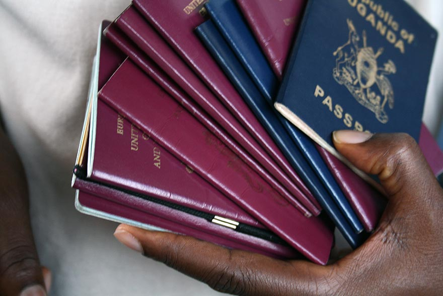 Close-up photo of a hand holding multiple passports.