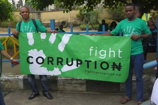Two men in green with a banner and the text fight corruption
