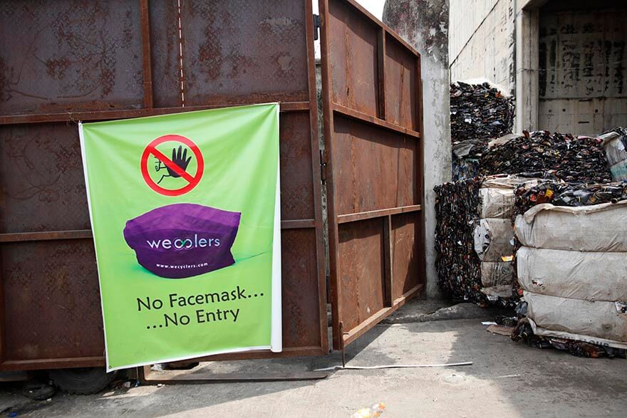 A banner informing workers of the compulsion to wear face masks to mitigate the risk of infection with the SARS-CoV-2 coronavirus that causes the pandemic COVID-19 disease hangs at the entrance of the Wecycler recycling and waste management hub in the Ebutte Metta neighborhood of Lagos, Nigeria 05 June 2020.