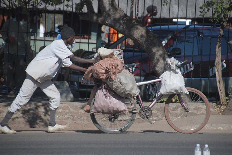 Trader pushes his bicycle loaded with sacks