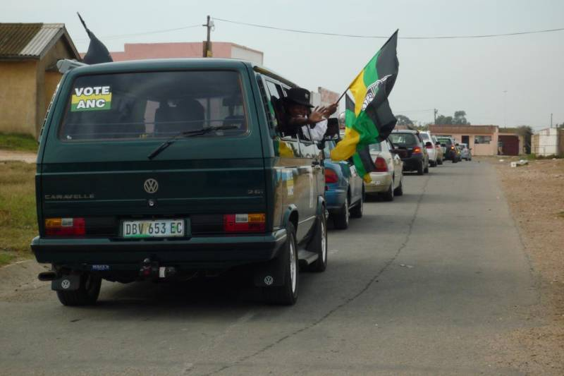 Back of a car with Vote ANC sticker and a person hailing an ANC flag through the window