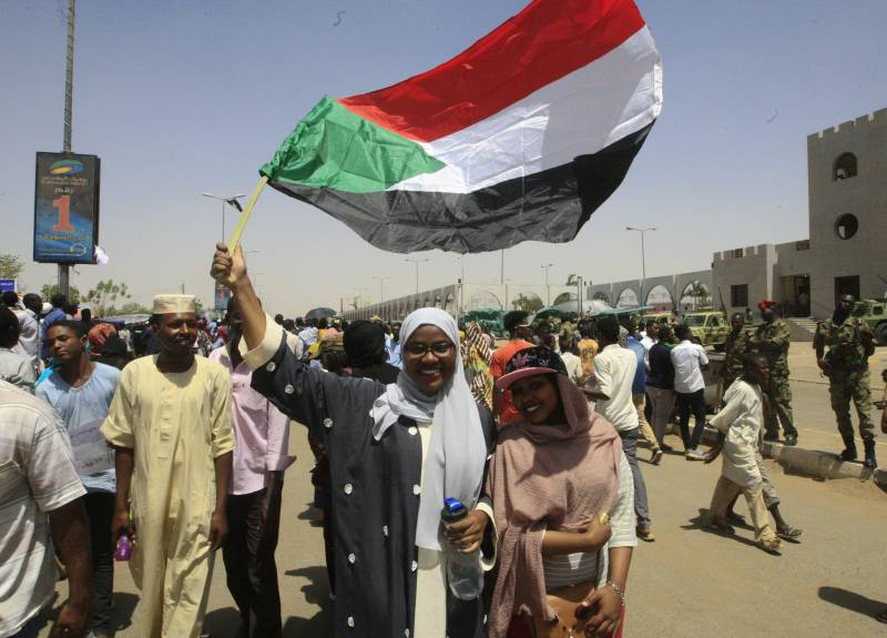 Women in a crowd waving a Sudanese flag
