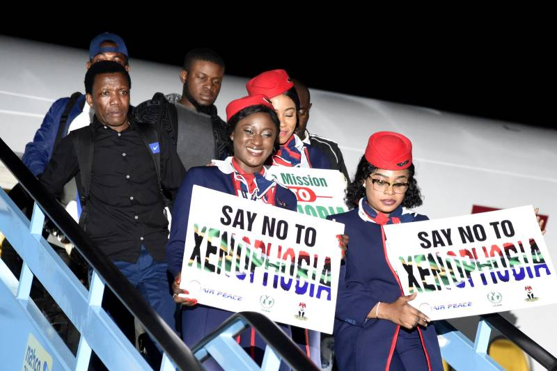 People exiting an airplane carrying signs of Say No To Xenophobia