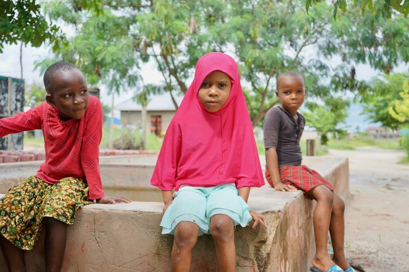 Three kids sitting outside in a village