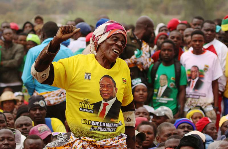 Supporters wait for President Emmerson Mnangagwa to address an election rally of his ruling ZANU (PF) party in Bindura, Zimbabwe. A woman rasing her arm in front
