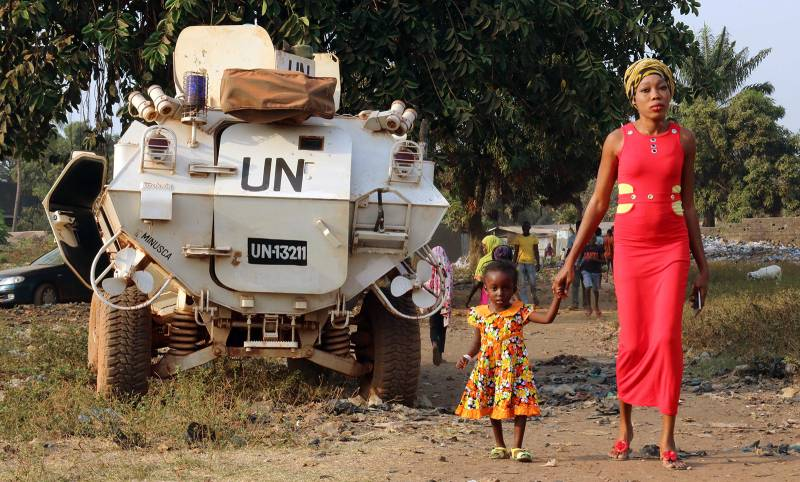 Mother and child in front of a military vehicle