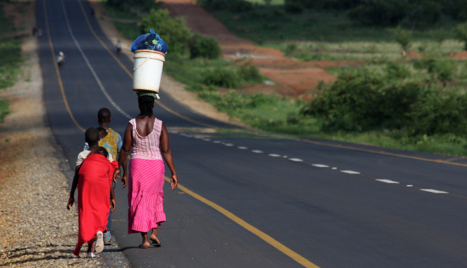 Woman with children walking down a road