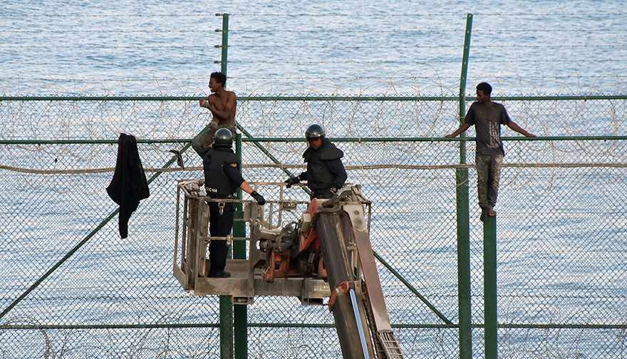 Spanish Civil Guard officers use a boom lift while African migrants sit on top of a border fence as they attempt to cross into Spanish territories, between Morocco and Spain's north African enclave of Ceuta, August 2019