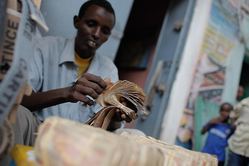 A money exchanger counts Somali shilling notes on the streets of the Somali capital Mogadishu