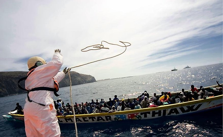 A person from the Spanish coastguard throws a rope to a fishing boat carrying African migrants