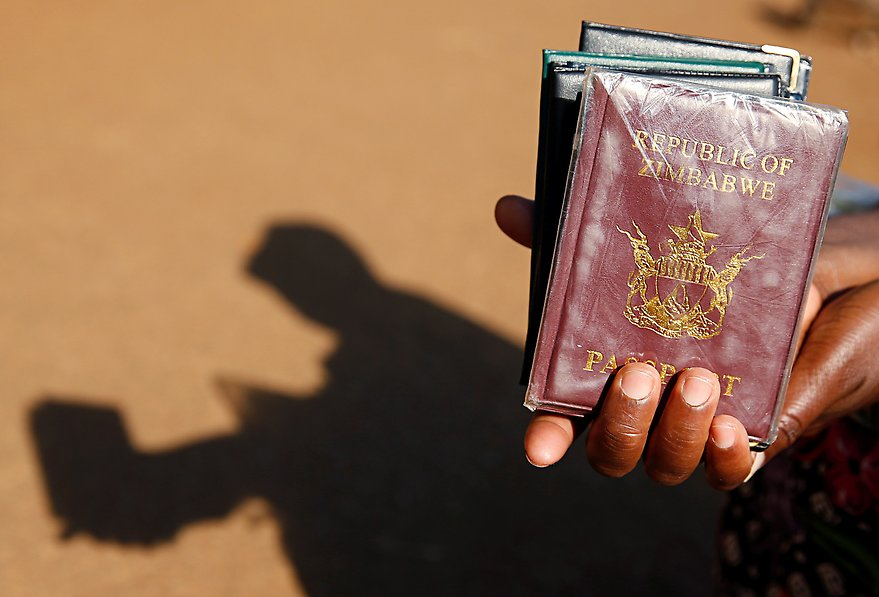 A street vendor offers passport covers for sale outside a Home Affairs Department office in Harare, Zimbabwe.